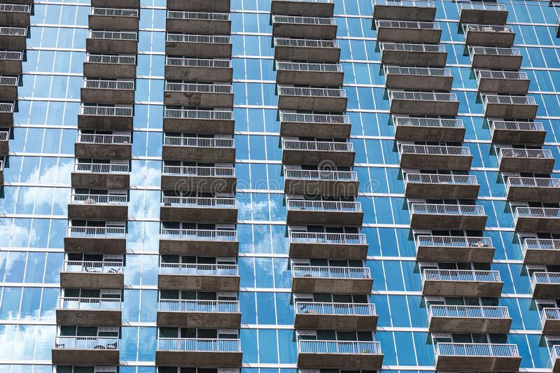 Rows of balconies forming a repetitive pattern on the facade of the modern high rise building made out of blue glass. stock image