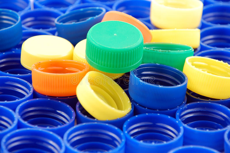 Rows of blue and colorful plastic lids - caps stock photography