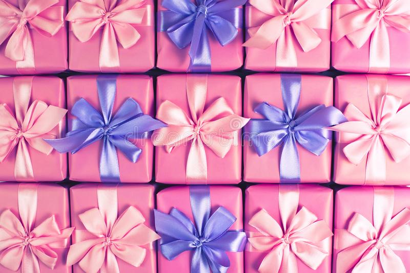 Rows of boxes with gifts decoration ribbon satin bow pink A top view of Flat lay toning stock photos