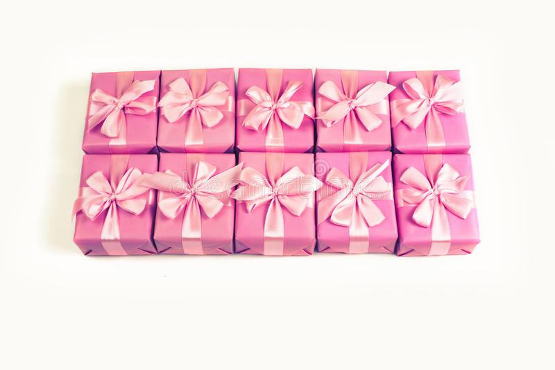 Rows of boxes with gifts decoration ribbon satin bow pink A top view of Flat lay toning. royalty free stock photo
