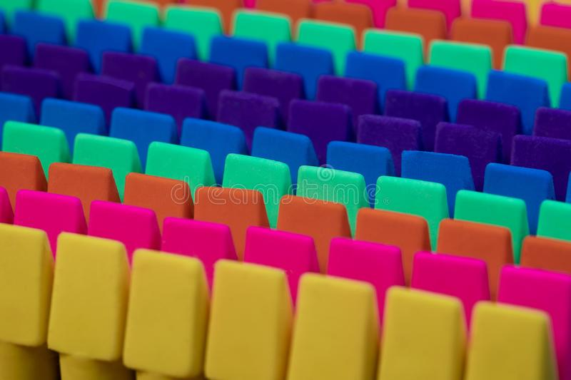 Rows of brightly colored pencil erasers lined up in an OCD order. Ly fashion with a high contrast lighting and a shallow depth of field and a tight framing stock photography