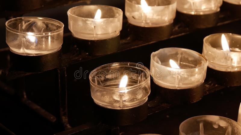 Rows of burning lit candles / tealights in Catholic Christian Church royalty free stock photo