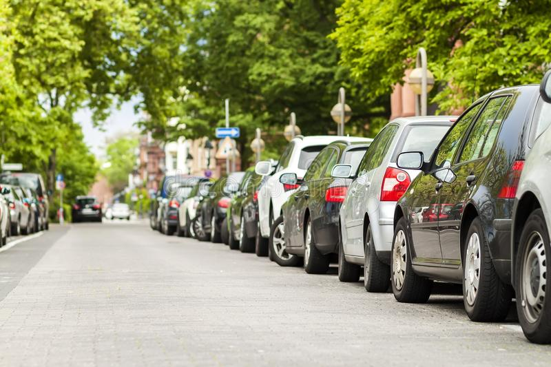 Rows of cars parked on the roadside in residential district royalty free stock image