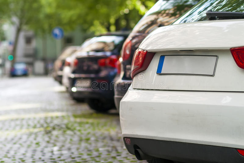 Rows of cars parked on the roadside in residential district stock photography