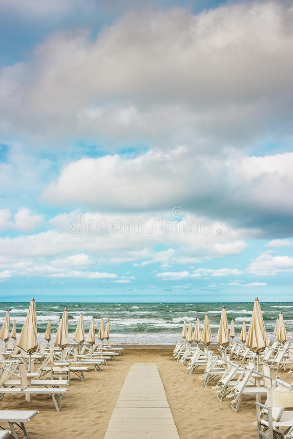 Rows of closed umbrellas and deckchairs on the empty beach stock photography
