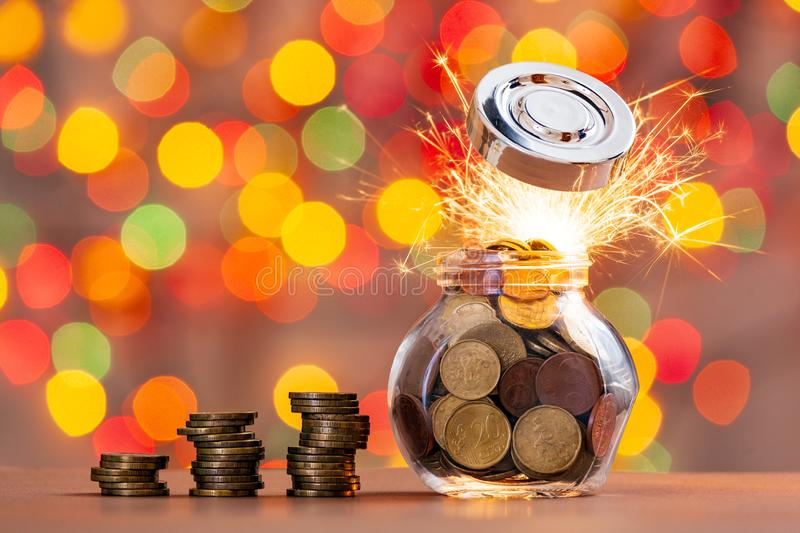 Rows of coins and a jar of coins on a table with a blurry shiny background. stock images