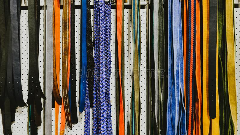 Rows of colorful belts in the shop for men and women. stock images