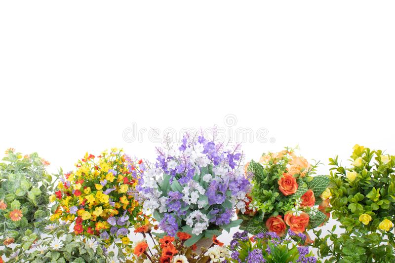 Rows of colorful fake flowers on white background, made from cloth and plastic for decoration.  stock photography