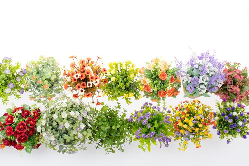 Rows of colorful fake flowers on white background, made from cloth and plastic for decoration. Taken form high angle, top veiw stock photos