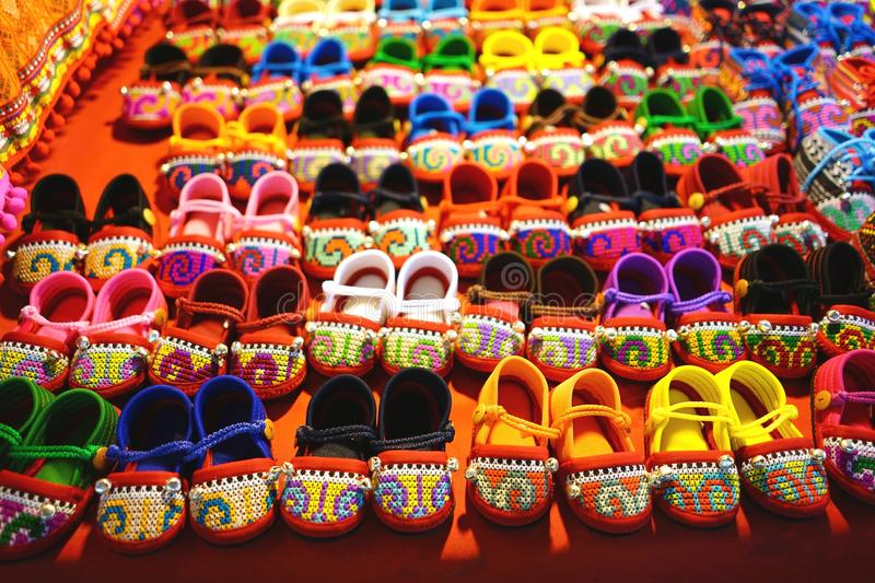 Rows of colorful hand made baby shoes in market stock image