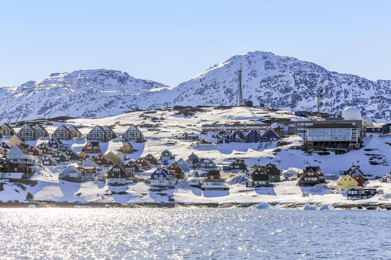 Rows of colorful Inuit houses along the fjord with snow mountain stock images