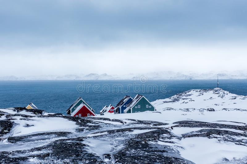 Rows of colorful inuit houses hiding in the rocks with fjord in royalty free stock images