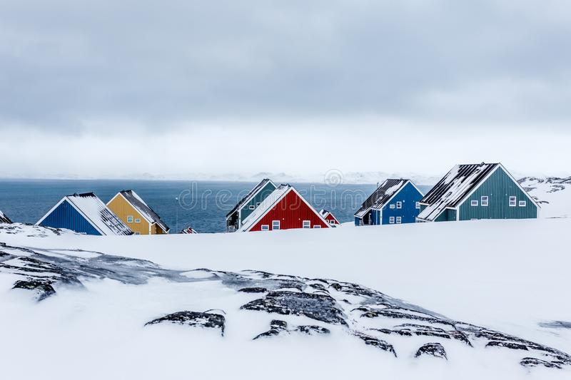 Rows of colorful inuit houses among rocks in a suburb of arctic stock image