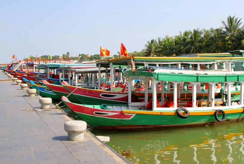 Rows colorful tourist cruise boats river, Hoi An. Rows of colorful wooden boats for tourists to make a river cruise in the port of ancient town Hoi An, Vietnam royalty free stock image