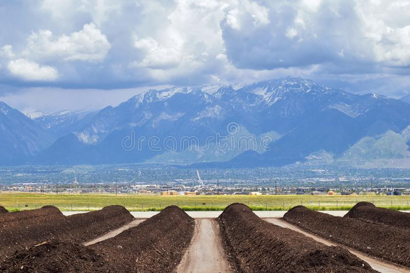 Rows of Compost ready for sale with Panoramic view of Wasatch Front Rocky Mountains, Great Salt Lake Valley in early spring with m. Elting snow and Cloudscape royalty free stock photography