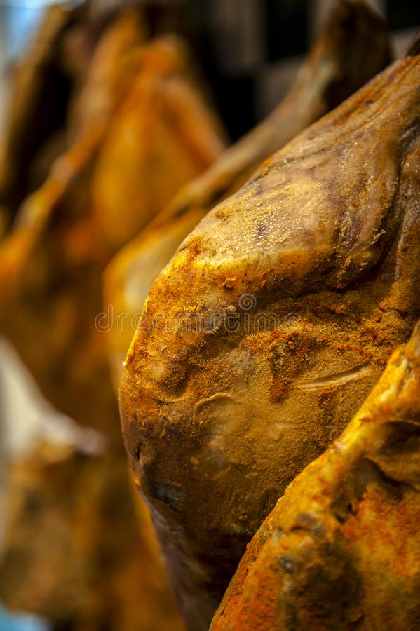 Rows of dried Italian dried ham in butchers shop. Traditional craftsman italian ham - home made salted and seasoned haunch of pork royalty free stock photo