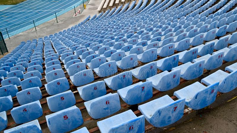 Rows of empty blue seats with numbers on the stadium stock photos