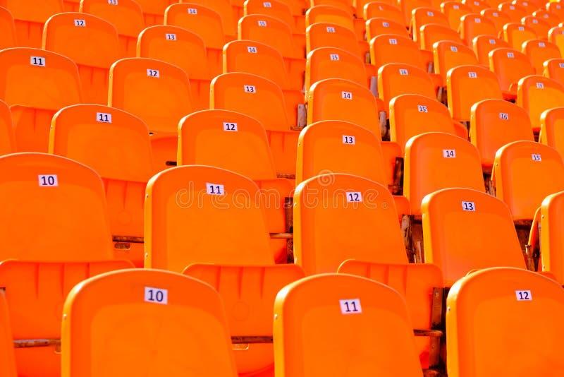 Rows empty bright oranje plastic seats in a stadium. Rows of empty bright orange plastic numbered seats in a stadium royalty free stock photography