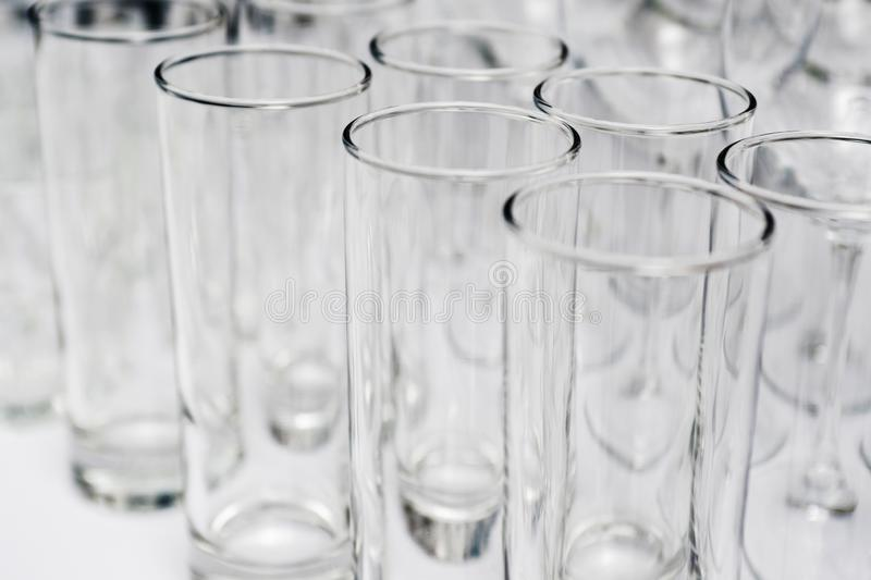 Rows of empty glasses close up. Glass goblets on the white table. Restaraunt bar concept royalty free stock photos