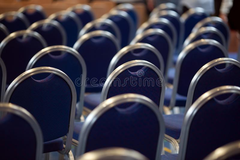 Rows of empty metal chairs in a large assembly hall.Empty chairs in conference hall.Interior meeting room. Back view royalty free stock image