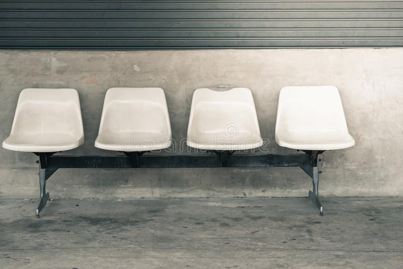 Rows four plastic seats and steel front factory. Wall concrete stock images