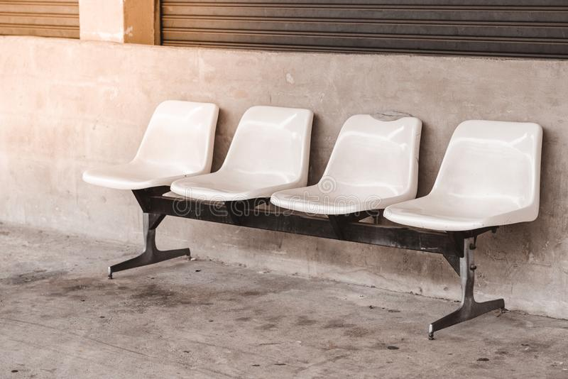Rows four plastic seats and steel front factory. With wall concrete royalty free stock image