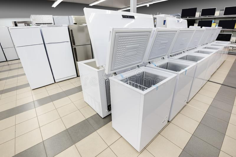 Rows of freezers and refrigerators in appliance store. Rows of white top loading freezers and fridges in appliance store`s showroom stock photo