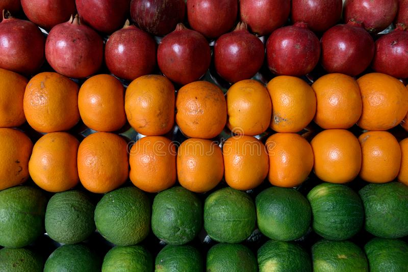 Rows of fresh harvested colorful fresh fruits, pomegranates, oranges and limes stock photos