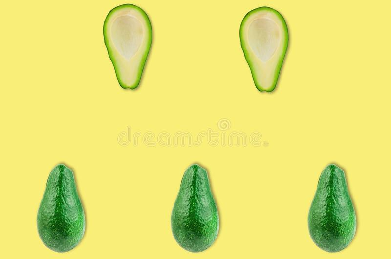 Rows of fresh wholes and halves of organic avocado without kernels in center of yellow table in kitchen or market stock photos