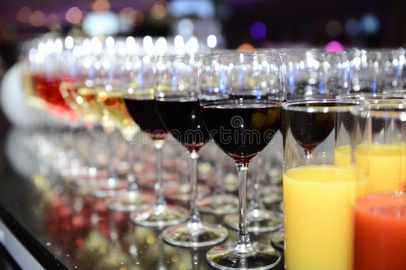 Rows of full champagne, sparkling wine and red wine glasses. Dining, drink. stock photography