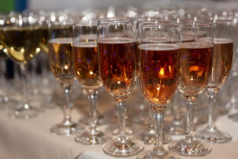 Rows of glasses with pink champagne on a festive buffet table. Exit registration of events. Close-up royalty free stock photos