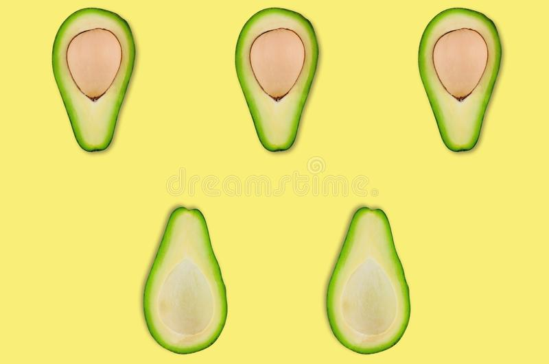 Rows of halves with and without kernels of organic avocado in center of yellow table in kitchen or market royalty free stock photos