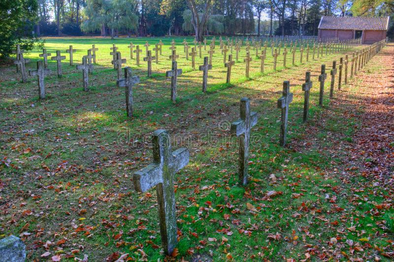 Rows of crosses in a graveyard. Rows of identical headstone stone crosses in graveyard, shades and sunlight, autumn leaves and grass stock photography