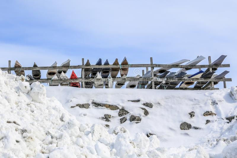 Rows of Inuit kayaks stored for a winter time, Nuuk old city harbor, Greenland. Arctic boat boats canoe canoeing cold eskimos fence frozen greenlandic kayaking stock photo