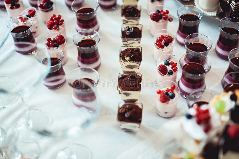 Rows of italian mignon cakes on a white cloth.  stock photos