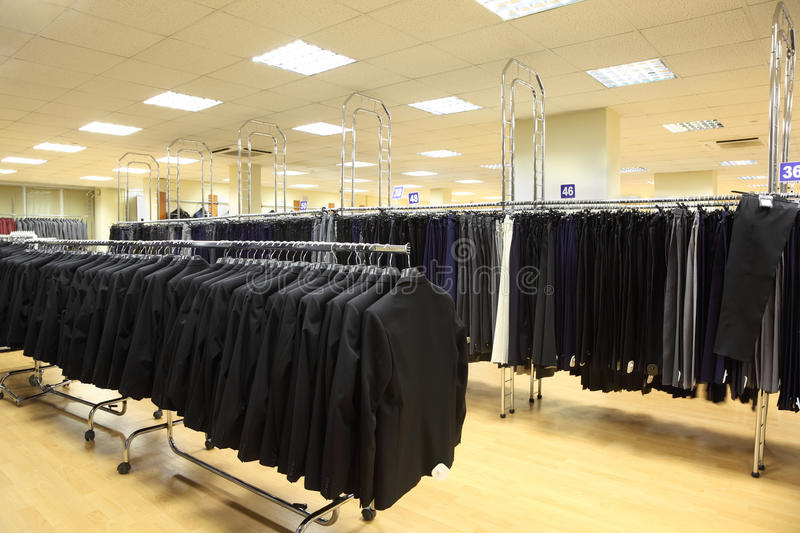 Rows of jackets and men trousers in shop