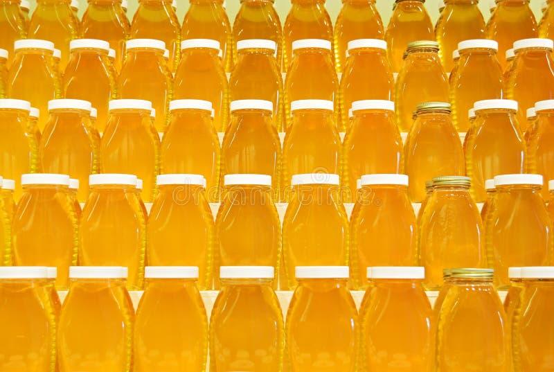 Jars of honey on shelves. Rows of jars of fresh honey on shelves stock images