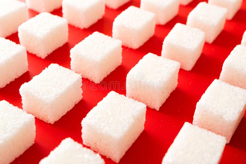 Rows of lump sugar on a brightly red background. Lots of sweet stock photos