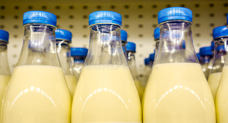 Rows of many plastic bottles with milk inside with blue covers against another milk bottles and metal background in the shop. Milk as dairy product for royalty free stock image