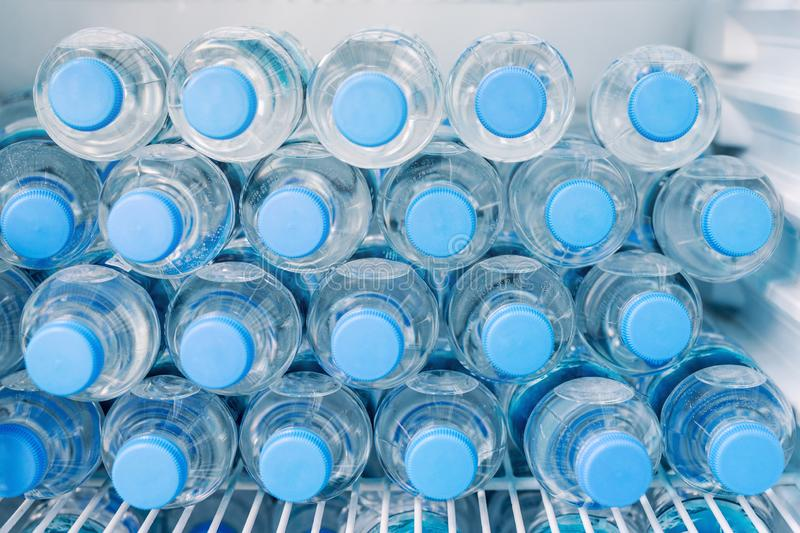 Rows of many transparent plastic bottles with drinking water supply in white refrigerator. Mineral water stack storage in fridge royalty free stock image