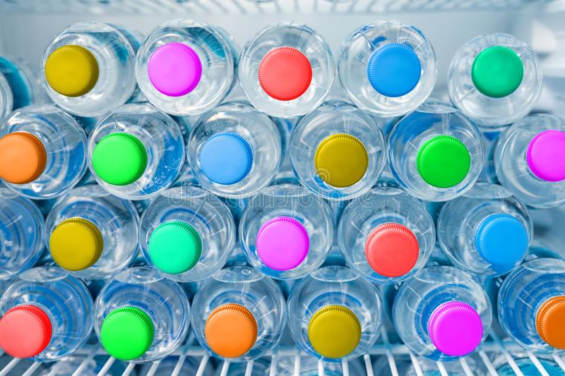 Rows of many transparent plastic drinking water bottles with bright multiclored colorful lids in white refrigerator. Mineral water. Stack storage in fridge stock photography