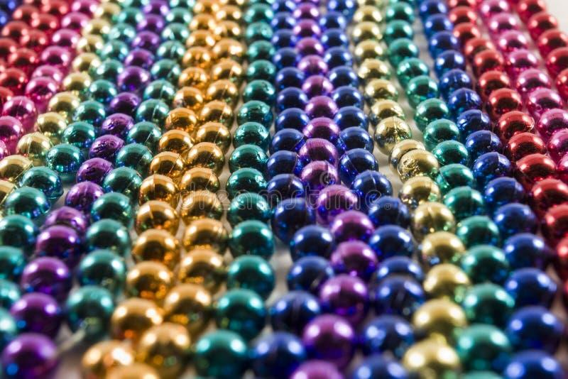Rows of Mardi Gras beads. Rows of multi colored Mardi Gras beads stock image