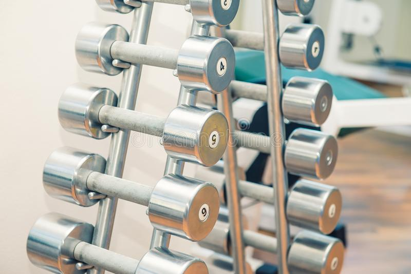 Rows of metal heavy dumbbells on stand in sport gym, physiotherapy clinic. Physical therapy center. Sports equipment for training. stock photo