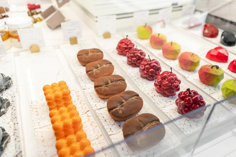 Rows of multicolored cakes and desserts in the window of a pastry shop. Modern mousse dessert, sweet snack. in the form stock photo