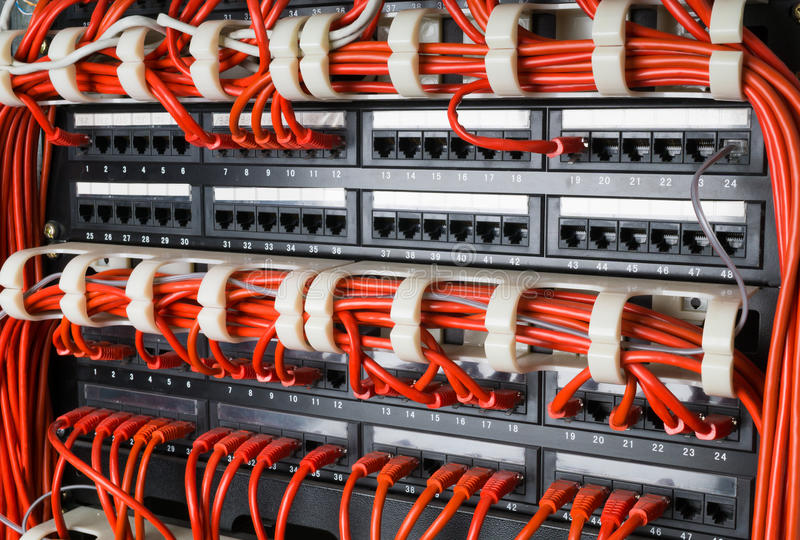 Rows of network cables connected to router and switch hub. Rows of red network cables connected to router and switch hub in server room at internet data center stock photo