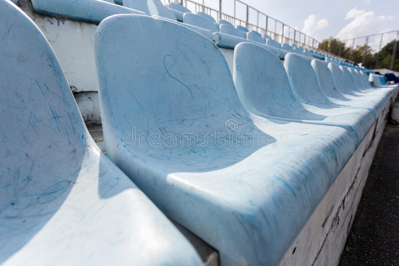 Rows of old plastic seats on empty stadium royalty free stock image