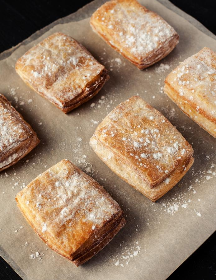 Rows of puff pastry cookies dusted with powdered sugar, vertical royalty free stock image