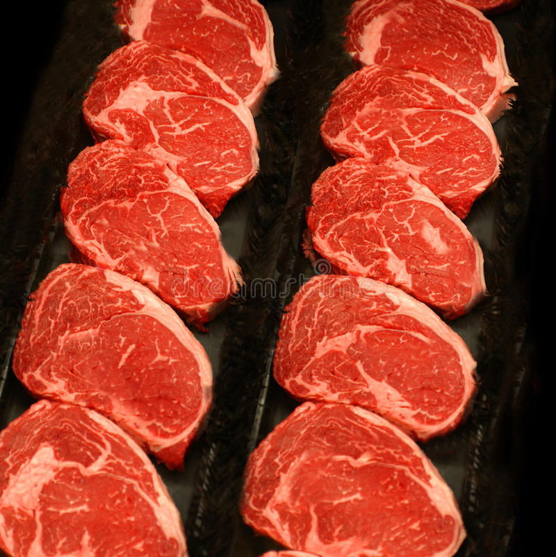 Rows of Raw Steaks in Meat Market royalty free stock image