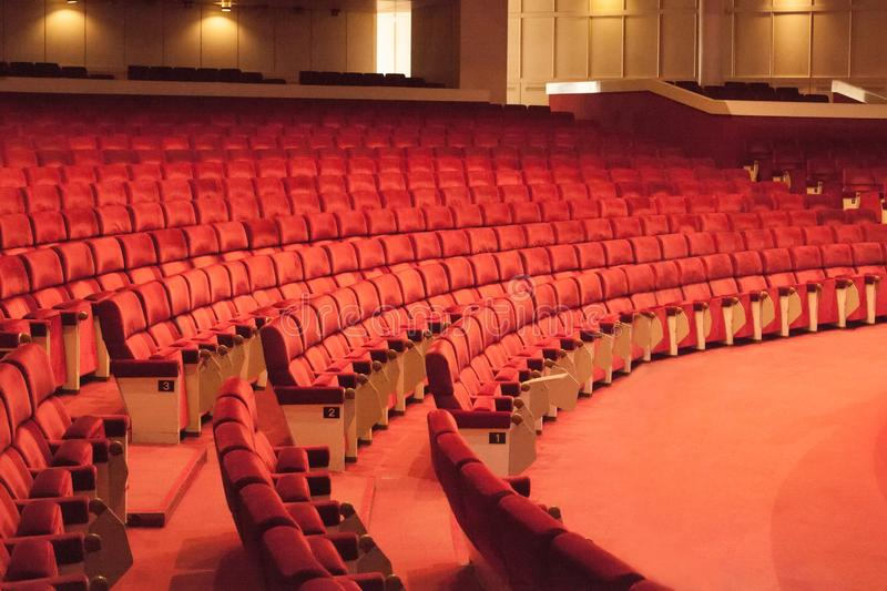Rows of red cinema seats. View of empty theater hall. Comfort chairs in the modern theater interior stock photo