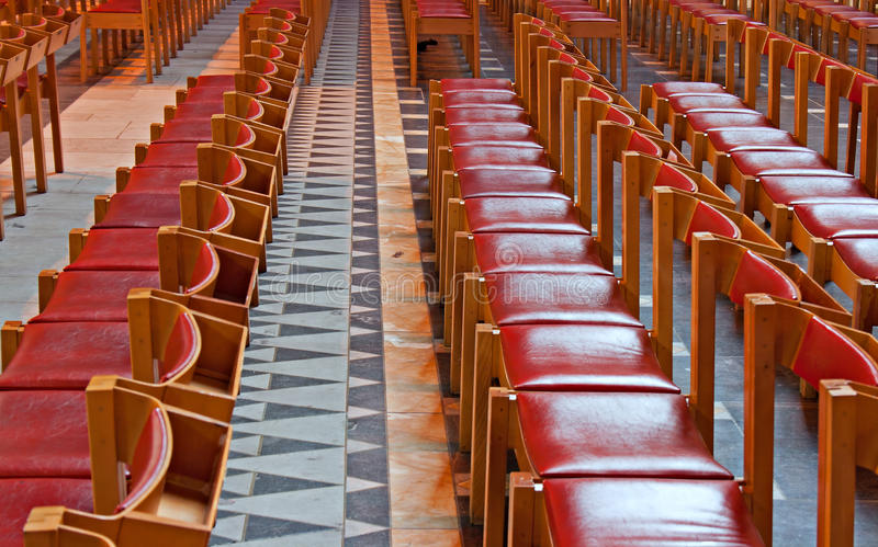 Rows of red wooden church pews